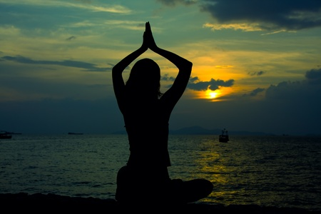 Healthy woman doing yoga outdoor, sunset over sea photo
