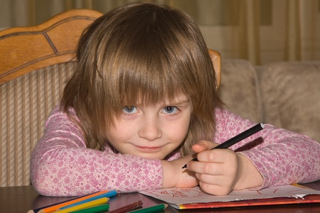 Little girl drawing with pencils at home photo