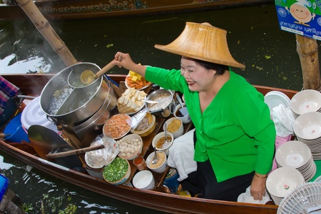 RATCHABURI, THAILAND - NOV 30: A woman makes Thai food at Damnoen Saduak floating market on November 30, 2011 in Ratchaburi, Thailand. Its popular for traditional style Thai food and old Thai culture. Stock Photo - 13365195