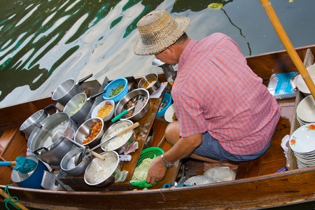 RATCHABURI, THAILAND - NOV 30: A men makes Thai food at Damnoen Saduak floating market on November 30, 2011 in Ratchaburi, Thailand. Its popular for traditional style Thai food and old Thai culture. Stock Photo - 13365445