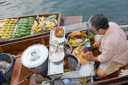 RATCHABURI, THAILAND - NOV 30: A woman makes Thai food at Damnoen Saduak floating market on November 30, 2011 in Ratchaburi, Thailand. Its popular for traditional style Thai food and old Thai culture. Stock Photo - 13365442