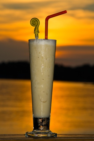 Fruit shake at sunset on the table photo