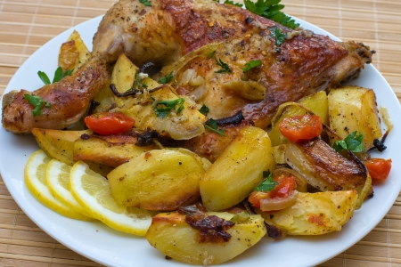 Fried chicken legs with tomato and potato served on the white plate Stock Photo - 13610577