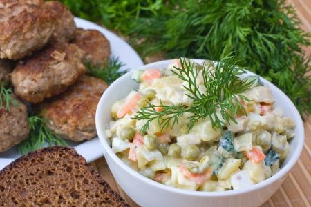 Russische traditionele salade Olivier in witte plaat Stockfoto