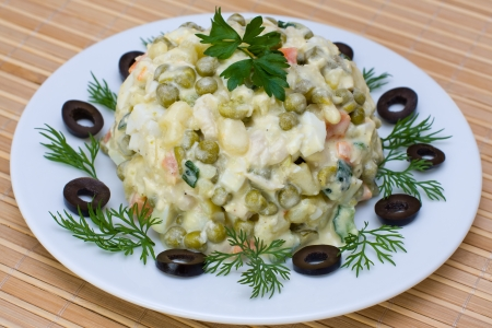 Russian traditional salad olivier in white plate
