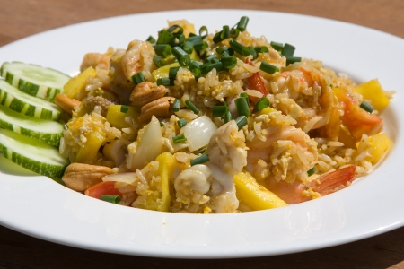 Rice with seafood, pineapple and vegetables on the plate photo