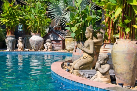 The stone Buddhist statues by the pool . Thailand .
