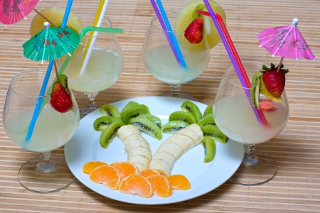 Fruit salad in the shape of palm trees, along with cocktails photo