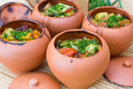 Meat baked with vegetables in rustic clay pot photo
