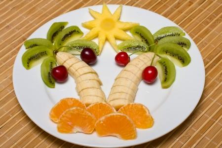 Creative fruit dessert with kiwi, banana,cherry and orange palm tree shape photo
