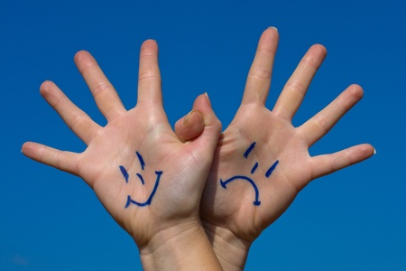 grievance: Linked hands with smiles and sadness pattern against the blue sky Stock Photo