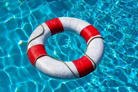 Life buoy in blue swimming pool Stock Photo