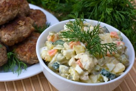 ensalada rusa: Tradicional ruso olivier ensalada en plato blanco Foto de archivo