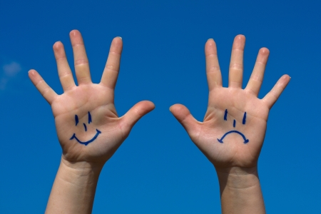 Hands with smiles and sadness pattern against the blue sky photo