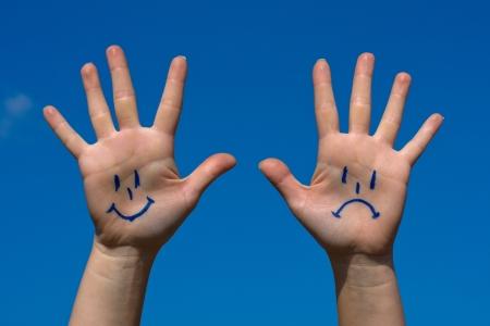 cabizbajo: Manos con sonrisas y el patr�n de tristeza contra el cielo azul
