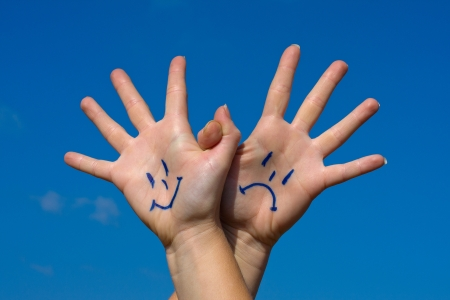 crestfallen: Linked hands with smiles and sadness pattern against the blue sky Stock Photo