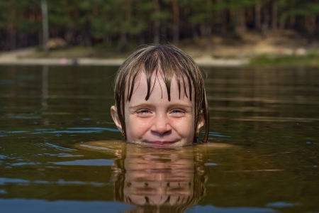 Closeup of young beautiful girl with beautiful smile in water photo