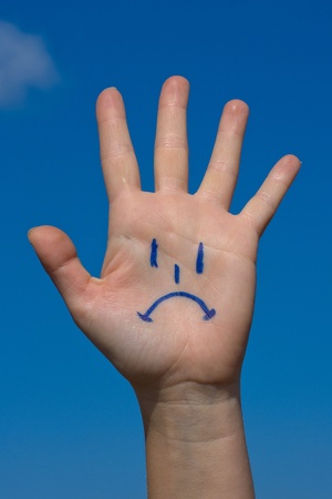 crestfallen: Human palm with sorrow pattern on blue sky background