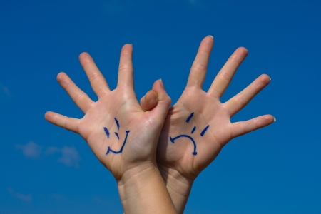 Linked hands with smiles and sadness pattern against the blue sky Stock Photo - 15608382