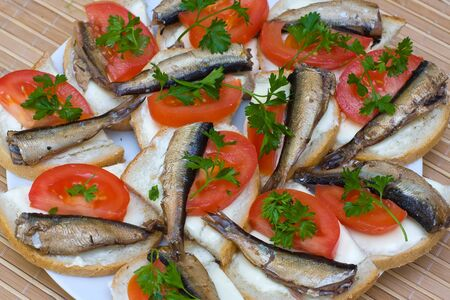 sprats: Sandwiches with sprats and tomatoes on a plate Stock Photo