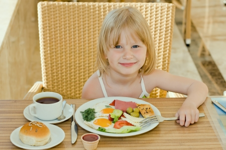 Little girl having breakfast photo