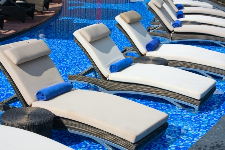lounges: Chaise lounges in swimming pool, Thailand Stock Photo