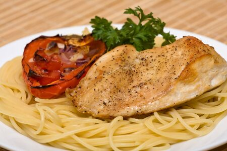 Spaghetti with chicken and vegetable on a plate photo