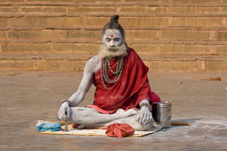VARANASI, INDIA - December 1: An unidentified naga baba sadhu sits on the ghat along the Ganges on December 1, 2012 in Varanasi, India. Tourism has drawn many alleged fake sadhus to Varanasi