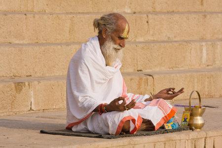 VARANASI, INDIA - DECEMBER 1: An unidentified sadhu sits on the ghat along the Ganges on December 1, 2012 in Varanasi, India. Tourism has drawn many alleged fake sadhus to Varanasi
