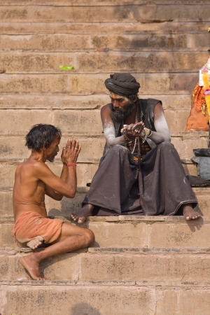 alleged: VARANASI, INDIA - DECEMBER 1: An unidentified sadhu and men sits on the ghat along the Ganges on December 1, 2012 in Varanasi, India. Tourism has drawn many alleged fake sadhus to Varanasi Editorial