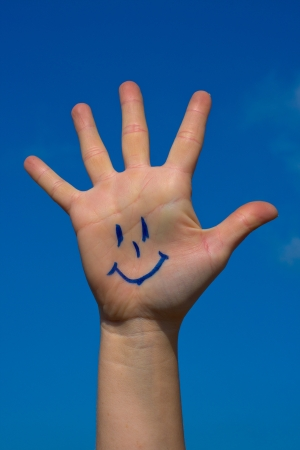 Human palm with smile on blue sky background photo