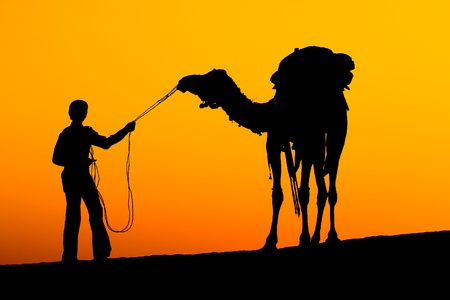 Rajasthan village. Silhouette of a man and camel at sunset in the desert, Jaisalmer - India photo