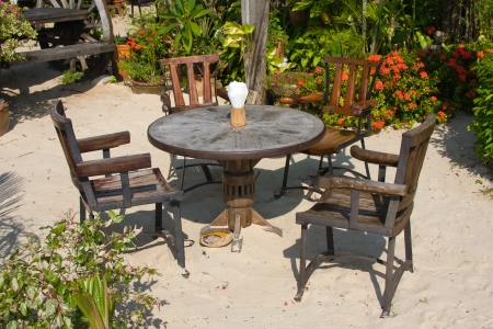 Table and chairs in a tropical garden on the shore, Thailand photo