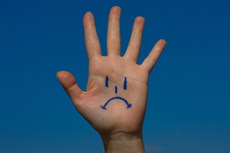 Human palm with sorrow pattern on blue sky background Stock Photo - 17432555