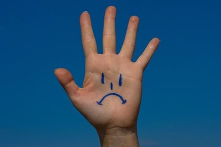 crestfallen: Palma de la mano humana con el patr�n de dolor sobre fondo de cielo azul