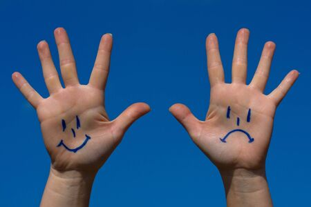 Hands with smiles and sadness pattern against the blue sky Stock Photo - 17474097
