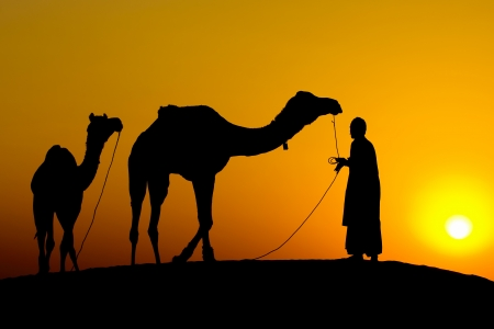 Rajasthan village. Silhouette of a man and two camels at sunset in the desert, Jaisalmer - India photo