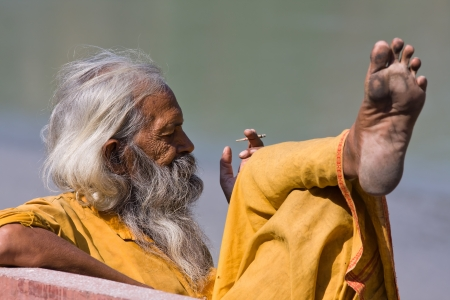 RISHIKESH, INDIA - OCTOBER 24: An unidentified portrait sadhu sits on the ghat along the Ganges on October 24, 2012 in Rishikesh, India.