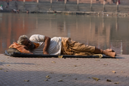 HARIDWAR, INDIA - NOV 8: An unidentified homeless man sleeps on the sidewalk near the River Ganges on November 8, 2012 in Haridwar, India. Poor Indians flock to Haridwar for charity. Stock Photo - 18469093