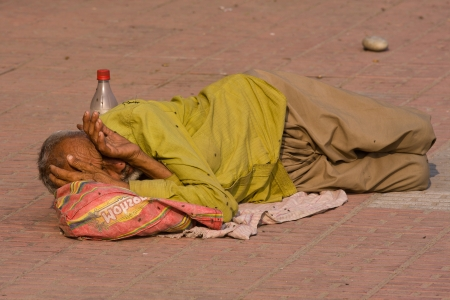 underprivileged: HARIDWAR, INDIA - NOV 8: An unidentified homeless man sleeps on the sidewalk near the River Ganges on November 8, 2012 in Haridwar, India. Poor Indians flock to Haridwar for charity.