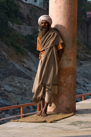 alleged: RISHIKESH, INDIA - OCTOBER 26: An unidentified sadhu stand on the ghat along the river Ganges on October 26, 2012 in Rishikesh, India. Tourism has drawn many alleged fake sadhus to Rishikesh Editorial