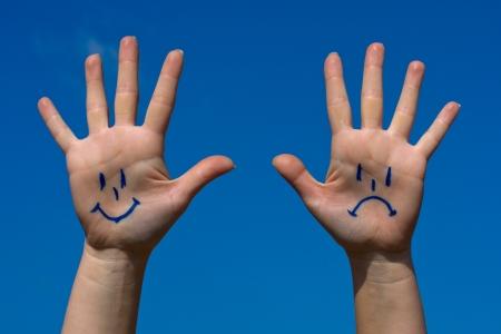 cabizbajo: Manos con sonrisas y el patrón de tristeza contra el cielo azul