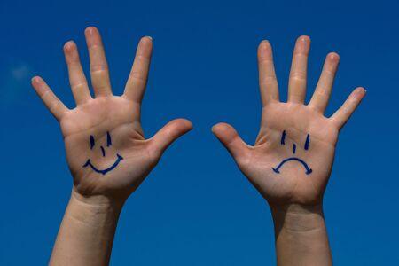 crestfallen: Manos con las sonrisas y el patr�n de tristeza contra el cielo azul Foto de archivo
