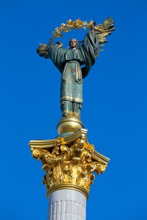 Independence monument in Kiev, Ukraine. This is a statue of an angel, made of copper, and gold plated, standing on a tall pillar, in the center of Kiev, Ukraine. photo