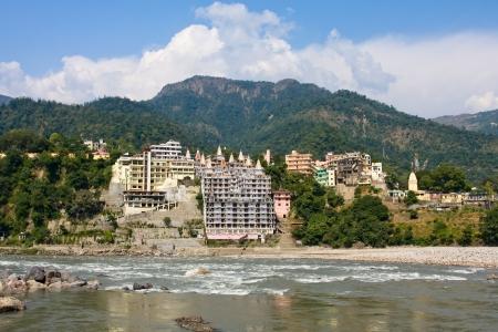 hindues: Santo r?o Ganges que fluye a trav?s de Rishikesh (la capital mundial del yoga) - la ciudad santa para los hind?es, la India. Foto de archivo