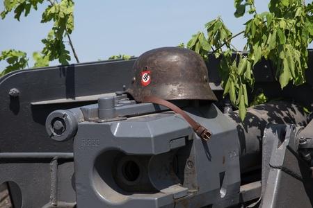 swastika: KIEV, UKRAINE - MAY 11 : Nazi helmet lies on the gun battle during historical reenactment of WWII on May 11, 20113 in Kiev, Ukraine