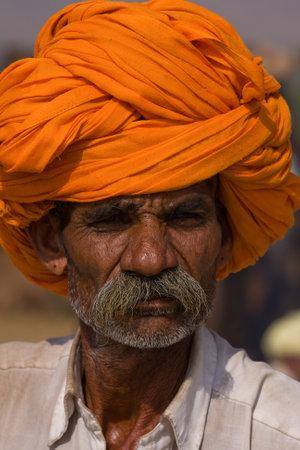 PUSHKAR, INDIA - NOVEMBER 19: An unidentified man attends the Pushkar Camel Mela on November 19, 2012 in Pushkar, Rajasthan, India. This fair is the largest camel trading fair in the world. Stock Photo - 20030480