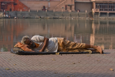 HARIDWAR, INDIA - NOV 8: An unidentified homeless man sleeps on the sidewalk near the River Ganges on November 8, 2012 in Haridwar, India. Poor Indians flock to Haridwar for charity.