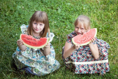 Cute two little girl eating watermelon on the grass in summertime photo
