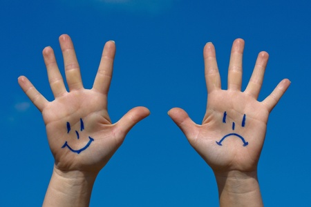 positivity: Hands with smiles and sadness pattern against the blue sky